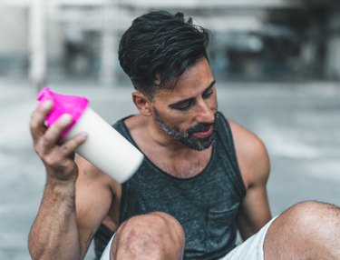 Fit man mixing protein shake after an outdoor workout