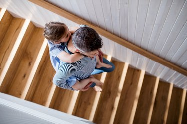 Top view of mature father and small daughter indoors at home, walking down stairs.