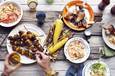 Mans hand picking up lamb and chicken skewer from table