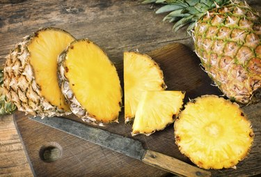 sliced pineapple on a wooden cutting board