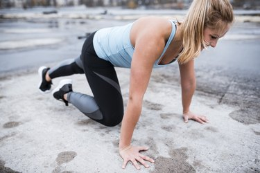Athlete woman doing mountain climbers outdoors