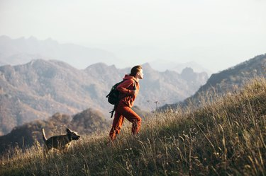 Beautiful woman traveler climbs uphill with a dog on a background of mountain views.