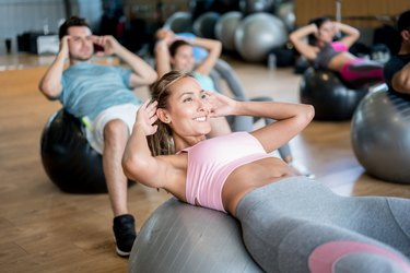 People at the gym in an exercise class using fitness balls