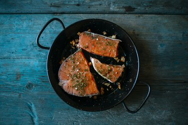 Salmon fillets in pan with parsley and garlic
