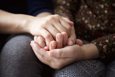 Hands of a senior woman and her daughter holding each other's hands together
