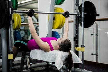 Fit woman lifting the barbell bench press