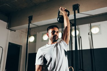Man working out with a kettlebell in a gym