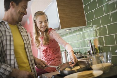 Father and daughter making pancakes