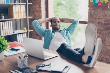 Young cheerful afro freelancer is resting at a workplace, with feet on top of the desk, with closed eyes, smiling, dreaming
