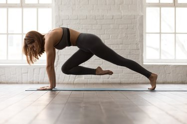 Woman practicing Pilates, doing Knee to Forehead exercise, Plank pose
