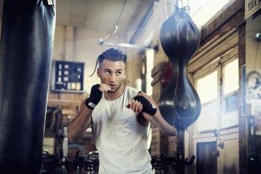 Hispanic man punching speed bag in gymnasium