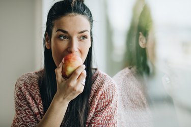 Pensive woman eating an apple by the window.