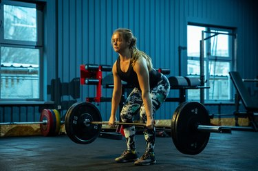 woman practicing deadlift for full lower-body workout