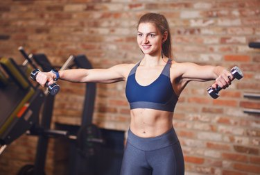 Portrait of attractive cheerful sportswoman with headphones in her ears. Sporty woman doing exercises with dumbbells for shoulders in the gym on the background of brick wall