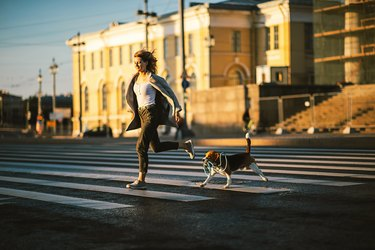 Energetic woman running on pedestrian way with dog in city