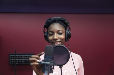 Smiling teenage girl musician recording music, singing in sound booth