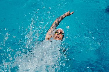Female with tattoos swimming backstroke in a pool