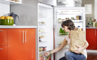Woman learning how to organize refrigerator with fridge organization tips