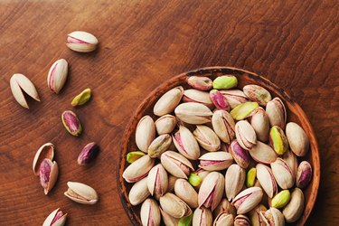 Bowl of pistachio nuts on wooden rustic table top view. Healthy food and snack. Vintage.