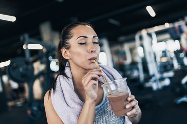 Young woman drinking glass of shake after workout in fitness gym