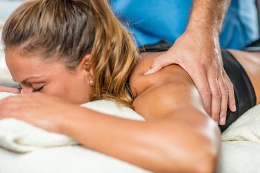 Sports massage in physical therapy. Therapist addressing trapezius muscle
