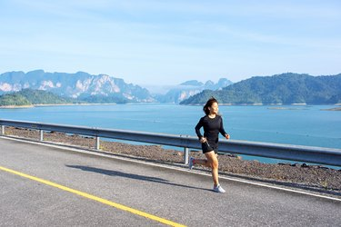 Asian woman running on road with mountain and lake background