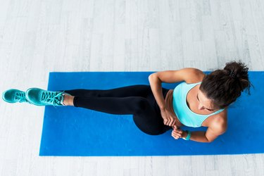 Top view of young fit woman working-out doing bicycle crunches on blue mat indoors.