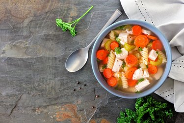 Homemade chicken noodle soup with vegetables, above on dark slate