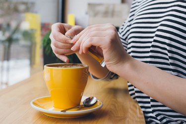 Girl pours sugar from a bag into a mug of coffee