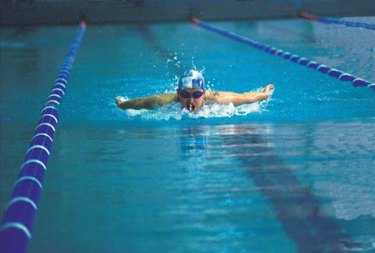 person swimming butterly in pool with lap lanes