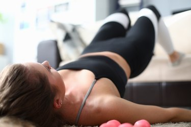 Woman performs sport exercise resting on sofa.