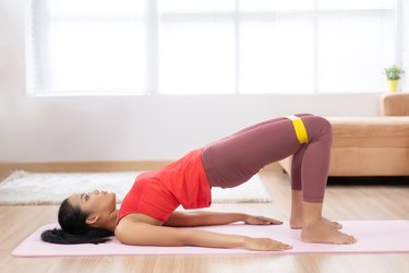 "Asian woman exercising at home on a yoga mat. She uses rubber resistance and pose ""Glute Bridge"""