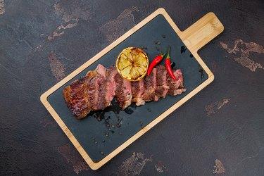 Beef steak sliced on dark concrete table