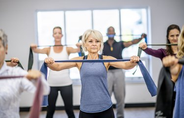 A workout class using resistance bands, focus on older woman