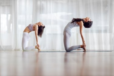 Side view of two fit caucasian girls in Camel yoga position. Yoga studio interior.