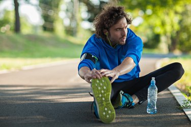 Man taking a break from exercising on a track to do some stretches for runners