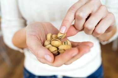 Young woman hands holding and picking up a pistachios nuts at home.
