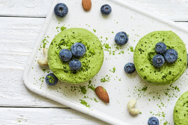 green matcha vegan raw cakes with blueberries, mint and nuts. healthy delicious food