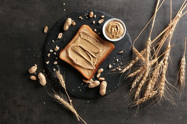 Slate plate with tasty toast and peanut butter on table