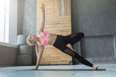 Woman in side plank pose at yoga class