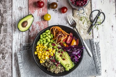 Quinoa vegetable bowl of avocado, Edamame, tomatoes, corn, carrots, red cabbage and pomegranate seed