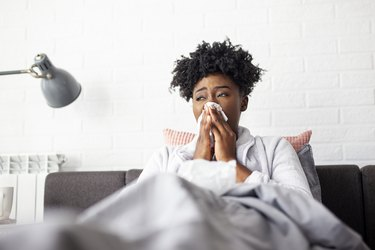 Woman lying in bed with virus and high temperature