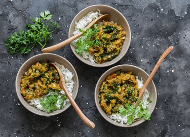 Burnt aubergine spinach vegetarian curry with rice on a dark background, top view. Indian cuisine