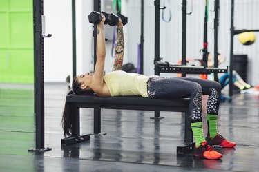 Athlete lifting dumbbells while lying on bench press in gym