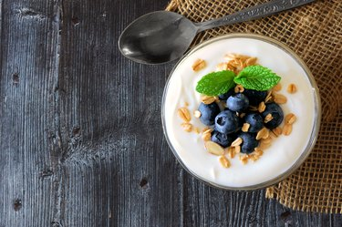 Yogurt with blueberries, granola, above view on rustic dark wood
