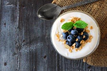 Yogurt with blueberries, granola, above view on rustic dark wood