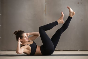 Young attractive woman doing bicycle crunches, grey studio backg