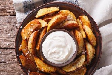 Tasty potato wedges with mayonnaise on a plate closeup. Horizontal