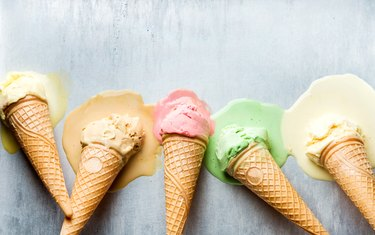 Colorful ice cream cones of different flavors. Melting scoops. Top view,  steel metal backgroun