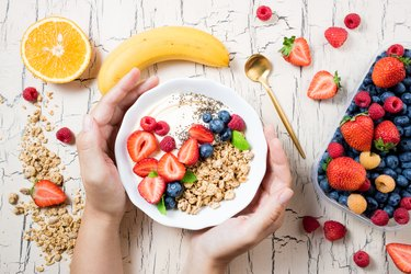 Women's hands holding granola with berries, fruits, yoghurt and coffee for breakfast. Cereal oats with strawberries, blueberries and raspberries for healthy eating. Top view